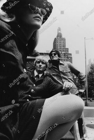 Two men and a woman posing at the Washington Square Arch in New York City; the man in the middle is wearing a cable-paneled Shetland sweater with pearl buttons, a shawl collar and shoulder epaulettes, by Himalaya, while the man in the sunglasses is wearing a London-trainman-inspired shirt with mattress ticking, brass-buttoned epaulettes and flapped chest pockets, by Surfboy.