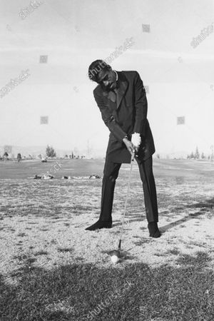 Sammy Davis Jr. wearing a black mohair suit with peak lapels and satin-faced peak-shawl collar and epaulettes, playing golf.
