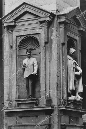 Model standing in a niche in Florence's Piazza del Mercato Nuovo, wearing Brioni's light blue wool gaberdine double-breasted blazer, with a gallon embroidered patch chest pocket, and two rows of white stitching; a colorful ship print dominates the silk lining.