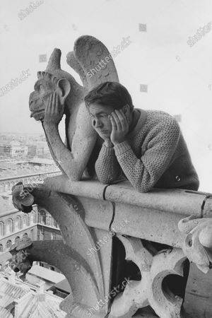 Model with his chin in his hands next to Notre Dame's gargoyle Le Penseur doing the same, wearing a bulky knit pullover of pale gold wool, with a ribbed crew neck and cuffs by Byford.