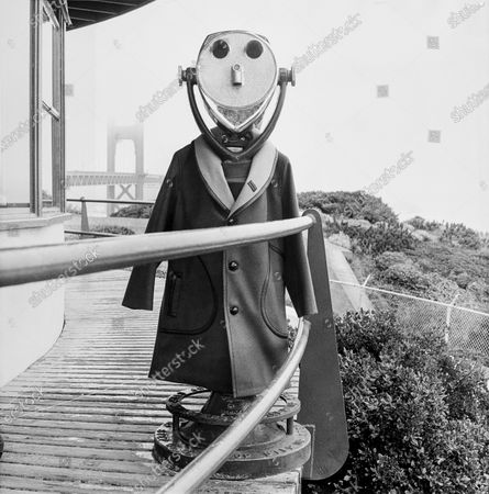 A panoramic viewer wearing a grey-green wool melton coat with a generous camel-colored collar edged in black leather by John Weitz for Lakeland, with San Francisco's Golden Gate bridge slightly obscured by mist in the background.