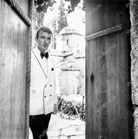 Male model in Greece wearing a white dinner jacket with black piping with shawl collar, angled pockets and side vents. Ivan Dodig