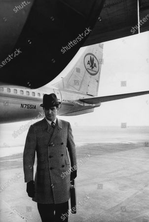 Male model on tarmac, standing in front of an American Airlines plane, holding a briefcase and wearing a black and white plaid wool topcoat with a military collar, set-in sleeves, angled pockets, a ticket pocket and deep side vents.