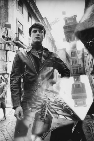 Male model posing in front of the Elevator de Santa Justa, built by M. Eiffel, and wearing a leather motorcycle jacket with a diagonal zip closure and buckle belted at the waist, by Ericson of Sweden.