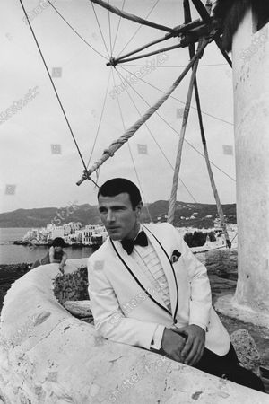 Male model posing on a terrace in Mykonos wearing a Dacron-and-rayon blended jacket with black satin trimming the shawl collars, by Formal Craft.