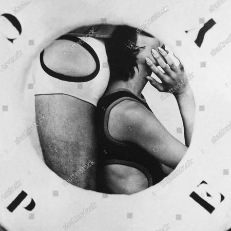 Profile image of a female model with her hand to her face, leaning against the backside of a male model, both of them in Nautical style bathing suits with side apertures by Rudy Gernreich.