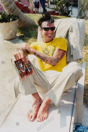 Stock Picture of Musician Tommy Lee sitting on a beach chair, holding a comic book and wearing a seersucker pants by Theory, a Chip and Pepper t-shirt and sunglasses by Marc Jacobs. Tommy Lee
