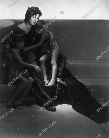 Award-winning actress Judith Anderson posing with two boy actors who play her children in the play Medea, and everyone dressed in Classical costume. Judith Anderson