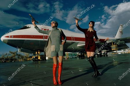 Two models posing on a tarmac in front of a Boeing 747 for TWA wearing, from left: a blue/ beige striped cotton dress with matching sweater and cap by Anna Modeller, enamel-framed sunglasses by Tropic-Cal and over-the-knee red patent boots by Latinas; right: maroon wool-jersey dress under a cardigan by Daniel Hechter for Jeune Couture, sunglasses by Roberts and black patent over-the-knee boots by Latinas.