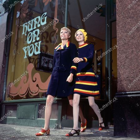English models, Sara Crichton-Stuart and Twiggy, walk down a city sidewalk; Sara wears a navy blue coat with striped red/blue/yellow collar; Twiggy wears a matching dress in navy blue with red/blue/yellow stripes around the skirt, cuffs and collar; both by Daniel Hechter for Bagatel.