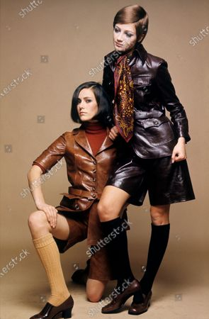 Two models pose together, one stands while the other kneels; model at left wears a short sleeved apricot-brown leather jacket with matching culottes and knee socks; model at right wears a long sleeved prune colored leather jacket with four front pockets with matching culottes and knee socks; jackets and culottes by Daniel Hechter for Moliter.