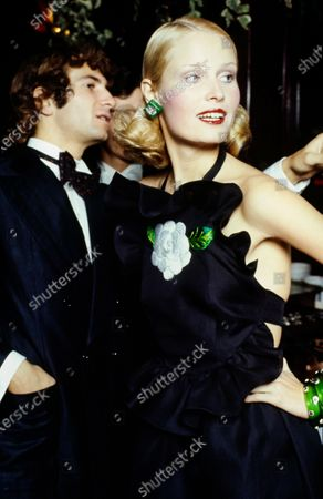 Upper-torso shot of French actor Gérald Falconetti, left, in a black taffeta dinner jacket by Cerutti 1881 with a white shirt and polka dot bow tie. Model Gunilla Lindblad, right, in a black halter backless evening gown with pinafore ruffles around the bodice, a white camellia embroidered center front, and a ruffled skirt flounce by Valentino. Accessories: green K.J.L. earrings, green William de Lillo bracelets. Hair by Jean-Louis David. Gérald Falconetti, Gunilla Lindblad
