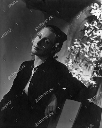 Seated portrait of actress Dame Judith Anderson (aka Frances Margaret Anderson) wearing a jeweled closure suit and cap. Judith Anderson