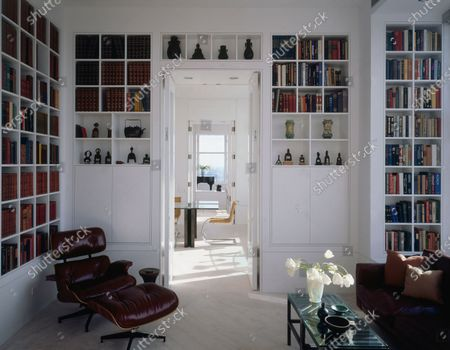 The library of a Chicago, Illinois apartment designed by architecture firm Tigerman McCurry, with a view to the dining and living rooms; Japanese bronzes over the door; custom sofa, Eames chair and ottoman in leather.