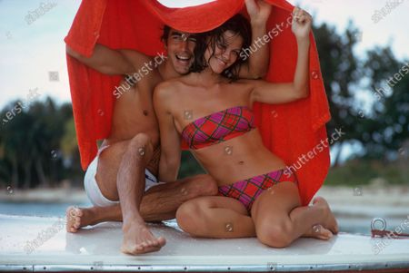 Stock Picture of Couple at the beach seated beneath an orange beach towel that they are holding over their heads. He wears white swim trunks. She wears a bandeau bikini by Monika for Elon in a red, hot pink and green plaid. Lisa Taylor