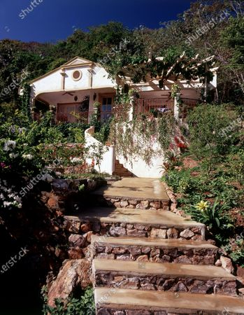 Stone stairs and garden landscaped by Tony Urrutia leading up to the Isla Taboga, Panama villa of interior designer Diane Burn. The villa's architecture is a mix of colonial, tropical and Mediterranean influences.
