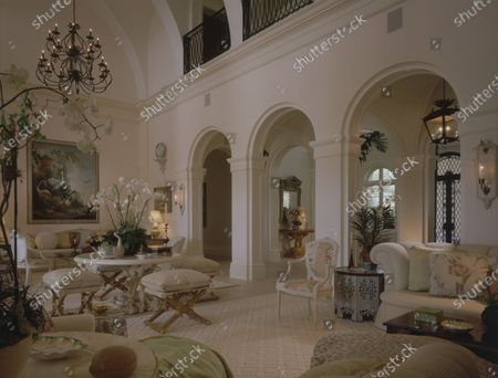 Living room in a house on Biscayne Bay in Florida designed by architect Jeffery W. Smith, with interiors by Mario Buatta, featuring a row of arched doorways leading into the room from the entry hall, a large painting of birds hanging over a white fringed sofa and a 1940s round root based table with a pot of white orchids on top.