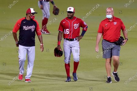 Washington Nationals center fielder Victor Robles (16) walks with manager Dave Martinez, left, as he leaves during the fifth inning of the team's spring training baseball game against the Houston Astros, in West Palm Beach, Fla