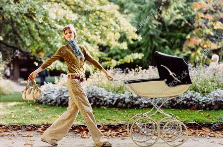 Model Stella Tennant walks in a Paris park wearing a Louis Vuitton ensemble while pushing a baby carriage. Stella Tennant