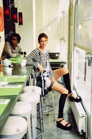 Model Stella Tennant sits in a Paris Cafe wearing a nautical knit ensemble. Stella Tennant