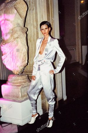 Model Stella Tennant wears a YSL satin suit, while standing next to statue. Stella Tennant