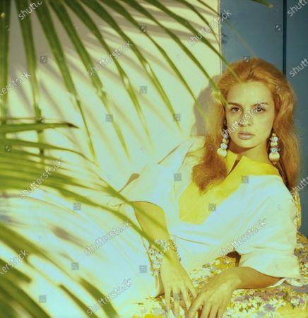 Future fashion designer, Carolina Herrera, reclines in the Hacienda la Vega, the family home belonging to her soon-to-be husband, Reinaldo Herrera Guevara. The Herrera home was located in the valley of Caracas, Venezuela. She wears a white caftan with a bright yellow neckline, and long drop earrings of woven gold and silver. Carolina Herrera