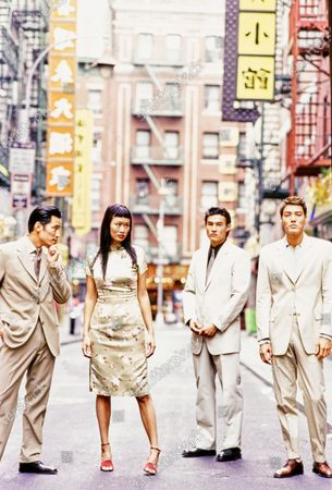 Standing in a street in New York City's Chinatown, are four Asian models, three male, wearing khaki colored suits. From the left: a three button wool twill suit from Canali and a silk tie with mini-dots by Pavone; a cotton and nylon two button suit by Calvin Klein with a black shirt and dolphin and chain patterned tie by Chanel; a two button side vent suit by Krizia Uomo with a grey polo shirt by Richard Edwards. The female model wears a beige brocade Mandarin dress from Pearl River Mart and red Walter Steiger sandals. So Yong Kim