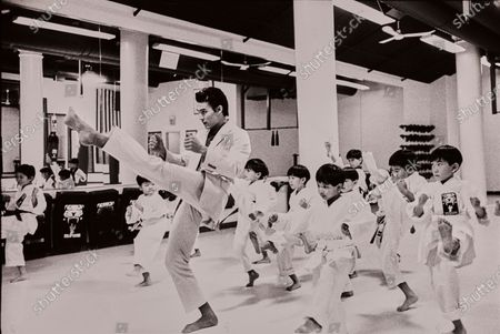 At Tiger Schulmann's Karate Center in New York City an Asian model leads a class of children in a kick. The model wears a khaki two-button cotton sack suit with a striped polo shirt, both from Nautica by David Chu.