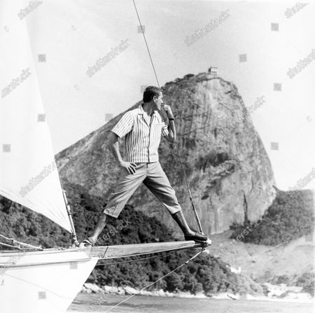 Model stands on a sailboat bowsprit, in Rio's Guanabara Bay (with Sugar Loaf mountain in the background) wearing a cotton twill shirt-jacket and deck pants by Alfred of New York.