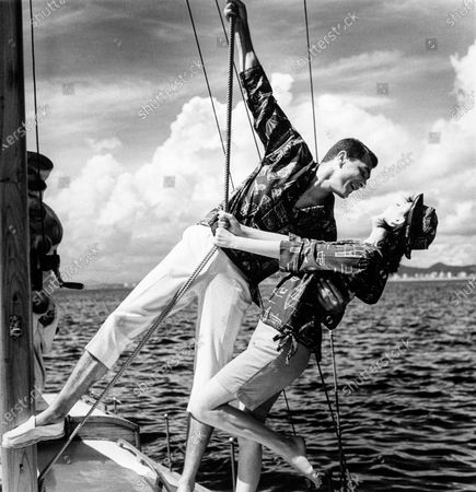 Model leans over the desk of a sailboat, with a female model, holding the rigging ropes, both wearing a sailboat print shirts by Bennett and espadrilles by Peerless.
