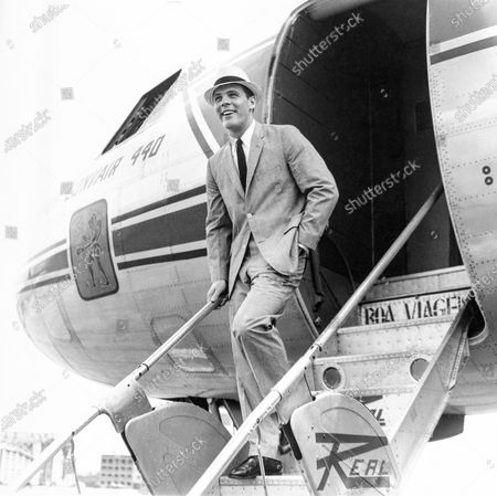 Model walks down a airplane stairway wearing a Dacron & cotton glen paid suit by Deansgate.