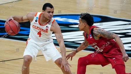 Clemson guard Nick Honor (4) protects the ball from Rutgers guard Jacob Young (42) during the first half of a men's college basketball game in the first round of the NCAA tournament at Bankers Life Fieldhouse in Indianapolis