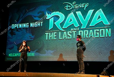 """Kelly Marie Tran, left, a voice cast member in """"Raya and the Last Dragon,"""" and co-director Carlos Lopez Estrada introduce a screening of the Disney animated film, in Los Angeles at El Capitan Theatre's reopening day following its shuttering more than a year ago due to the coronavirus pandemic. Theater reopenings are part of the entertainment industry's gradual road to recovery as states begin loosening restrictions"""