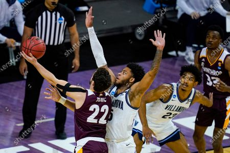 Winthrop guard Kyle Zunic (22) shoots over Villanova guard Justin Moore (5) in the first half of a first round game in the NCAA men's college basketball tournament at Farmers Coliseum in Indianapolis