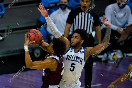 Winthrop guard Adonis Arms (25) shoots over Villanova guard Justin Moore (5) in the first half of a first round game in the NCAA men's college basketball tournament at Farmers Coliseum in Indianapolis
