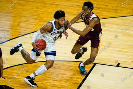 Villanova guard Justin Moore (5) drive son Winthrop forward Chase Claxton (33) in the first half of a first round game in the NCAA men's college basketball tournament at Farmers Coliseum in Indianapolis