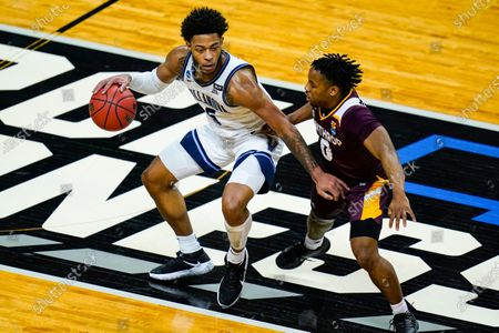 Villanova guard Justin Moore (5) drives on Winthrop guard Russell Jones Jr. (0) in the first half of a first round game in the NCAA men's college basketball tournament at Farmers Coliseum in Indianapolis