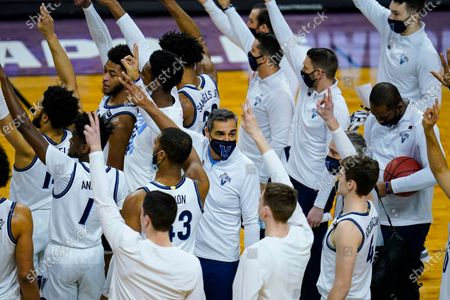 Villanova head coach Jay Wright and his team wave to fans following their win over Winthrop in a first round game in the NCAA men's college basketball tournament at Farmers Coliseum in Indianapolis, . Villanova defeated Winthrop 73-63