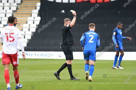 Carlisle United defender George Tanner (2) is shown a yellow card, booked by Referee Brett Huxtable during the EFL Sky Bet League 2 match between Stevenage and Carlisle United at the Lamex Stadium, Stevenage