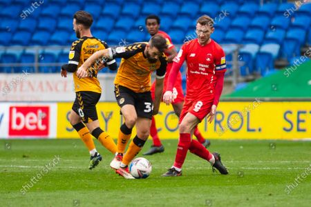 Joe Ledley of Newport County holds off Craig Clay of Leyton Orient