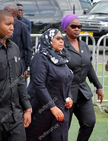 Tanzania's new President Samia Suluhu Hassan, center, arrives to pay her respects as the body of former president John Magufuli lies in state at Uhuru stadium in Dar es Salaam, Tanzania . Magufuli, a prominent COVID-19 skeptic whose populist rule often cast his country in a harsh international spotlight, died Wednesday aged 61 of heart failure, it was announced by Vice President Samia Suluhu Hassan, who was sworn-in as the country's new president on Friday