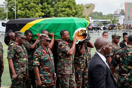 Members of the military carry the body of former president John Magufuli to lie in state at Uhuru stadium in Dar es Salaam, Tanzania . Magufuli, a prominent COVID-19 skeptic whose populist rule often cast his country in a harsh international spotlight, died Wednesday aged 61 of heart failure, it was announced by Vice President Samia Suluhu Hassan, who was sworn-in as the country's new president on Friday