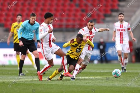 Stock Photo of Youssoufa Moukoko of Borussia Dortmund  is put under pressure by Ismail Jakobs (L) and Ellyes Skhiri (R) of 1.FC Koeln during the German Bundesliga soccer match between 1. FC Koeln vs Borussia Dortmund at RheinEnergieStadion in Cologne, Germany, 20 March 2021.