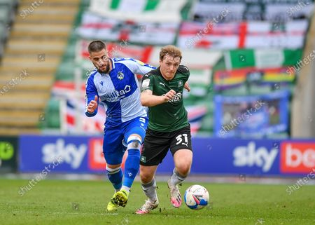 Plymouth Argyle Forward Luke Jephcott (31) runs with the ball and attacking and under pressure  from Bristol Rovers defender Max Ehmer (5)  during the EFL Sky Bet League 1 match between Plymouth Argyle and Bristol Rovers at Home Park, Plymouth