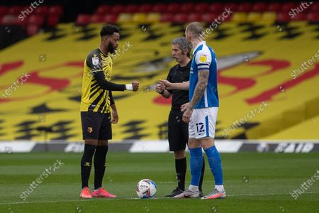 Captain Nathaniel Chalobah of Watford (left) bumps fists with Captain Harlee Dean of Birmingham City (right) and the referee Darren Bond
