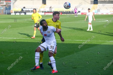 Hayden Carter of Burton Albion (17) heads clear from Cameron Jerome of Milton Keynes Dons (35) during the EFL Sky Bet League 1 match between Burton Albion and Milton Keynes Dons at the Pirelli Stadium, Burton upon Trent
