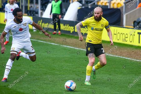 Cameron Jerome of Milton Keynes Dons (35) and John Brayford of Burton Albion (2) battle for the ball during the EFL Sky Bet League 1 match between Burton Albion and Milton Keynes Dons at the Pirelli Stadium, Burton upon Trent