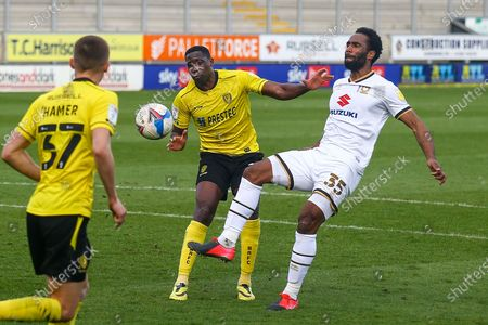 Cameron Jerome of Milton Keynes Dons (35) and Lucas Akins of Burton Albion (10) battle for the ball during the EFL Sky Bet League 1 match between Burton Albion and Milton Keynes Dons at the Pirelli Stadium, Burton upon Trent