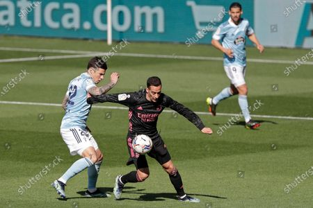 Celta Vigo's Santi Mina, left, challenges for the ball with Real Madrid's Lucas Vazquez during a Spanish La Liga soccer match between Celta and Real Madrid at the Balaidos stadium in Vigo, Spain