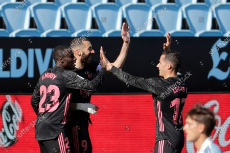 Real Madrid's Karim Benzema, 2nd left, celebrates with Ferland Mendy, left and Lucas Vazquez after scoring his side's second goal during a Spanish La Liga soccer match between Celta and Real Madrid at the Balaidos stadium in Vigo, Spain